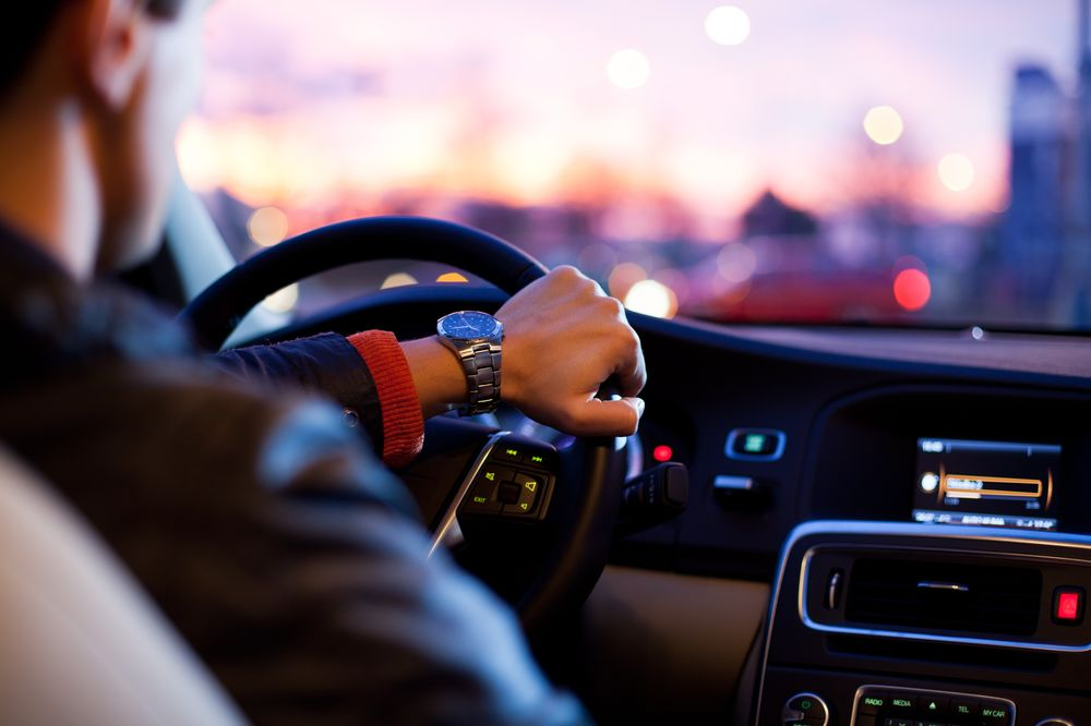 A man with watch, hand on steering wheel, dashboard lights