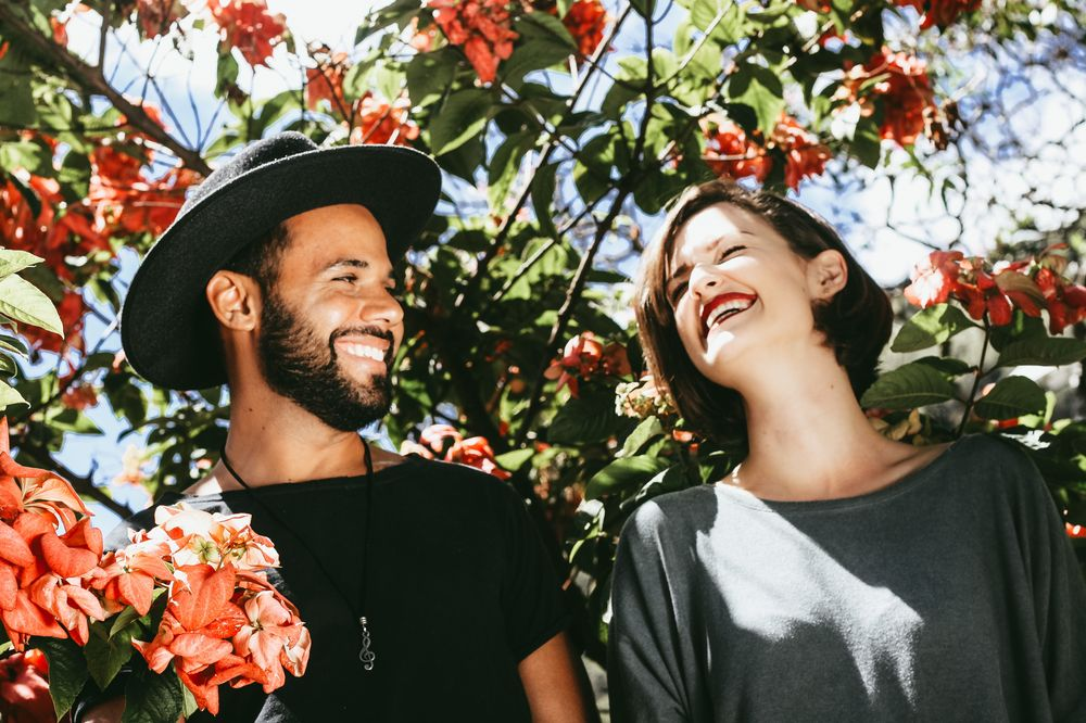 A smiling couple outdoors with trees in background