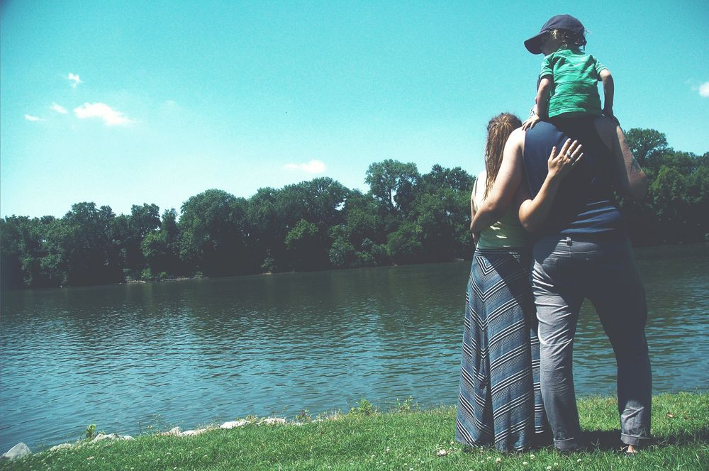 Couple and child looking out on the banks of a lake