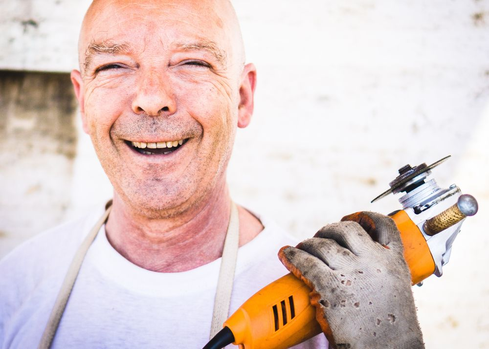 Happy smiling skilled worker holding his tool