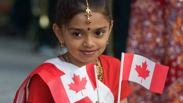 Young Indian child holding the Canadian flag