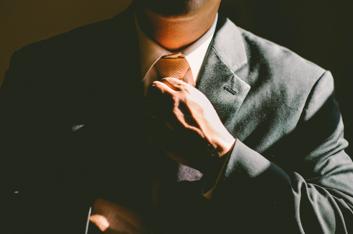 businessman pulling up tie