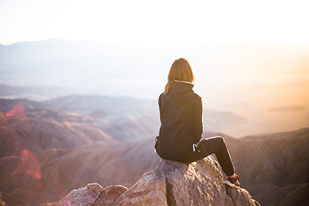 female hiker sitting on moutain summit during sunrise