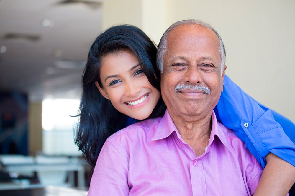 A father and daughter looking happy and smiling