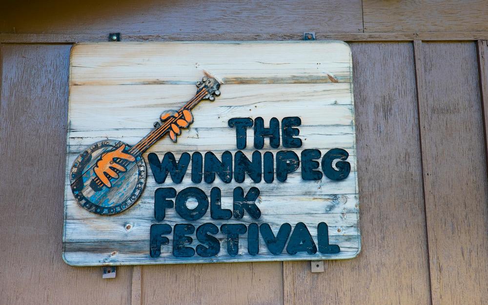 wooden sign about the winnipeg folk festival