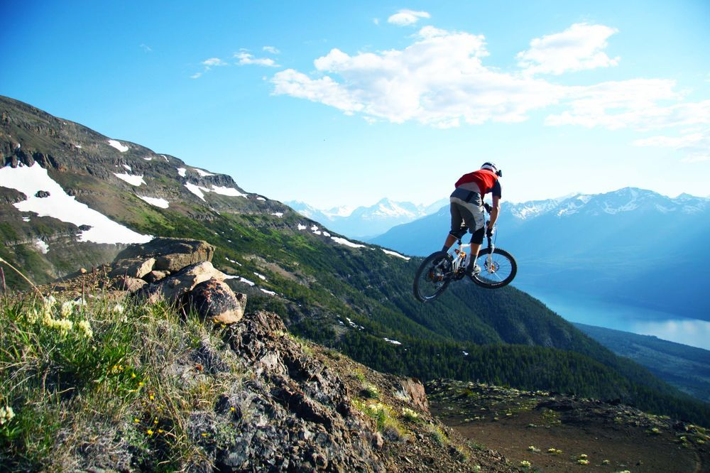 A sport enthusist jumps up while mountain biking