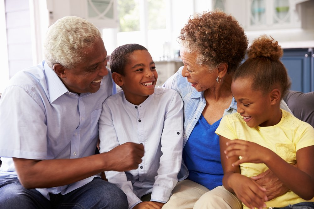 An elderly couple having a laugh with their grandchildren