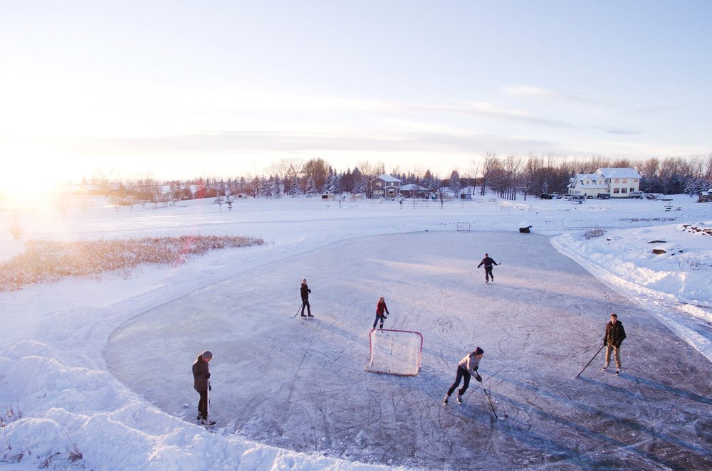 Game of ice hockey on frozen pond Canada
