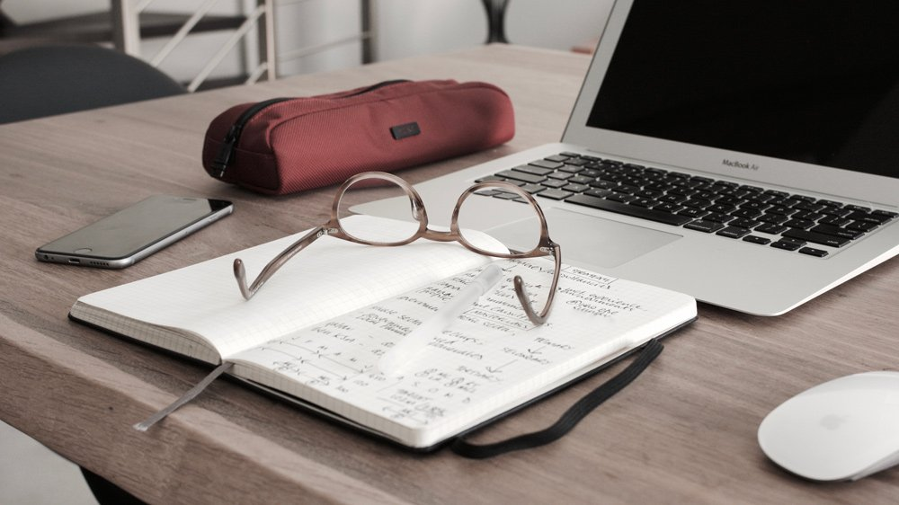 Student laptop with glasses and notebook