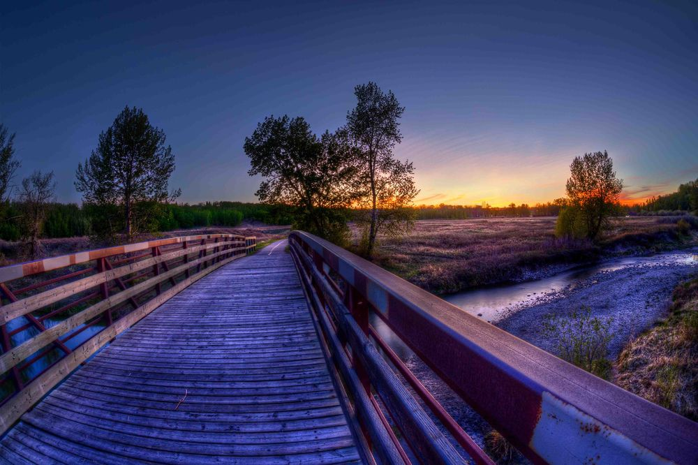A bridge over a river in Calgary at dusk