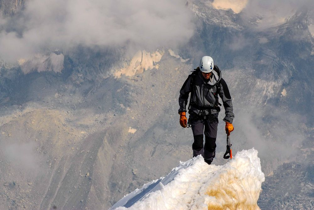 man climbing up glaciers on mountains