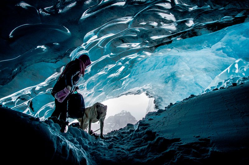 Woman explores glacier cave in Banff National Park with her dog