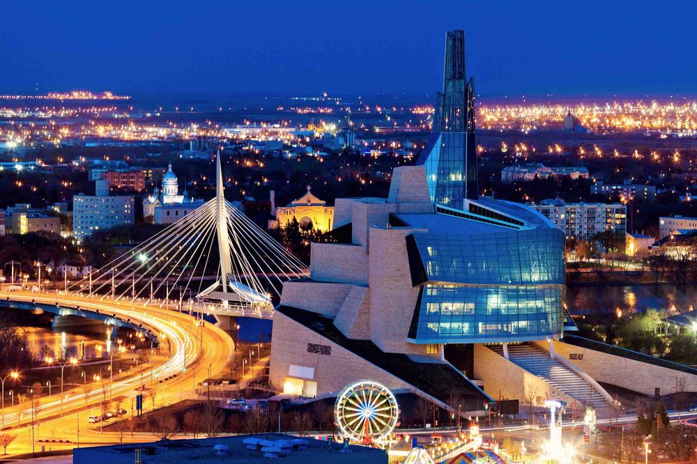 Night time view over the city of Winnipeg, with the Canadian Museum for Human Rights (CMHR) and its iconic Tower of Hope.