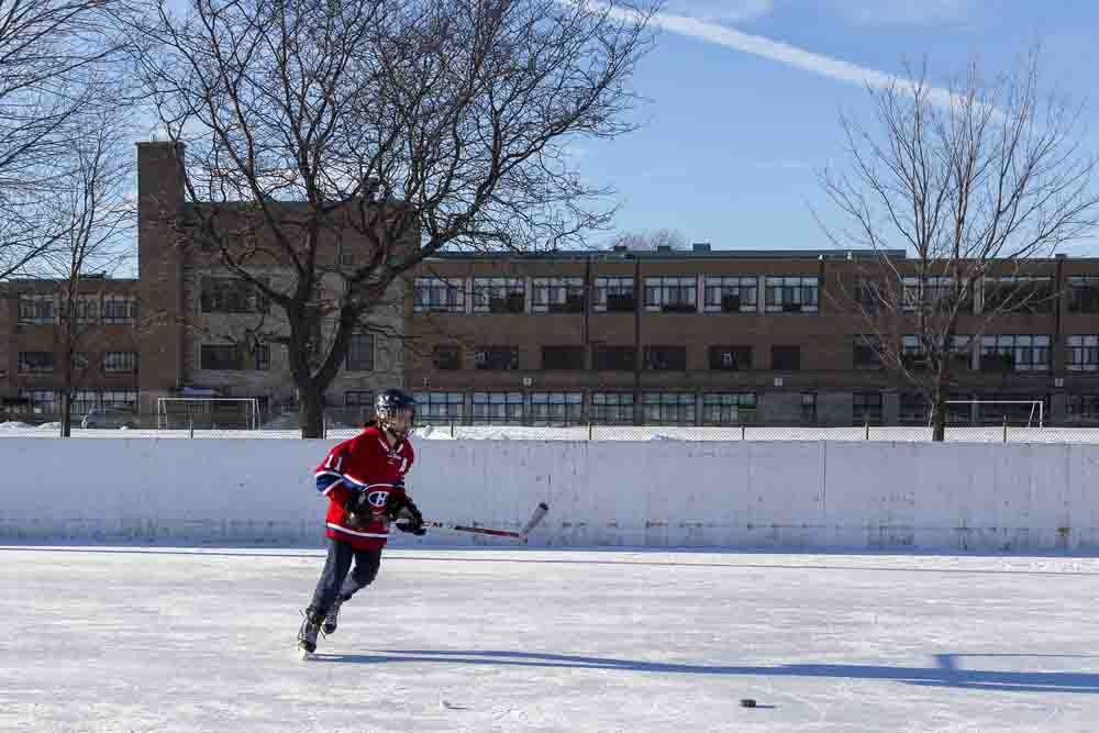A young person playing ice hockey in school yard