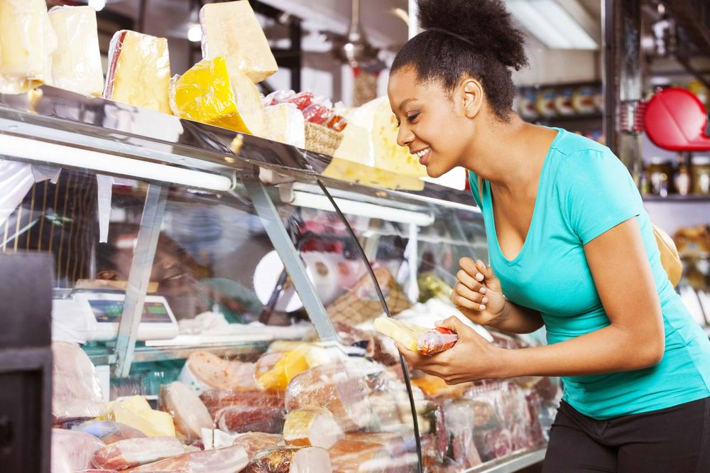 young woman choosing cheese from deli