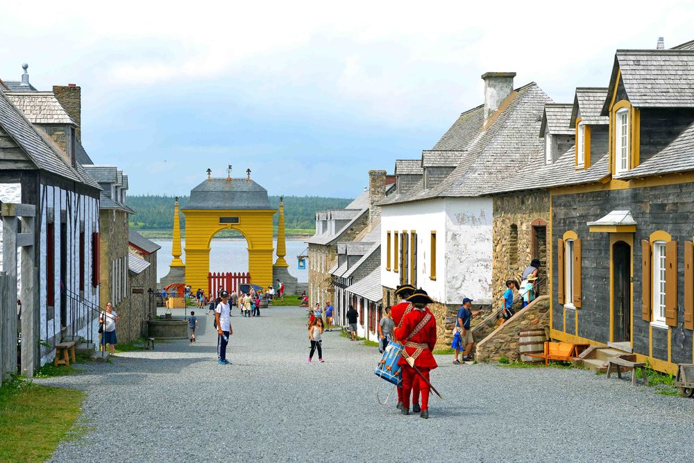 group of actors in costume walk down the main street of the Fortress of Louisbourg