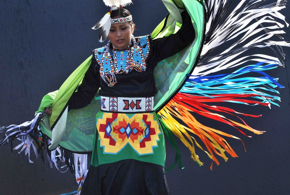 A young native american women perform a traditional dance for her audience