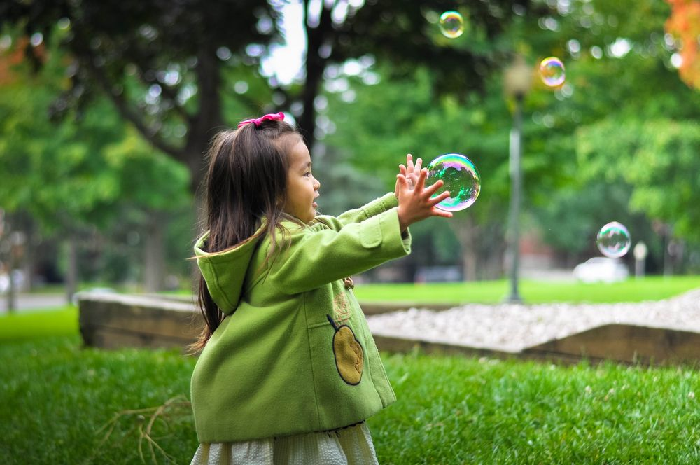 young Asian child chasing bubbles