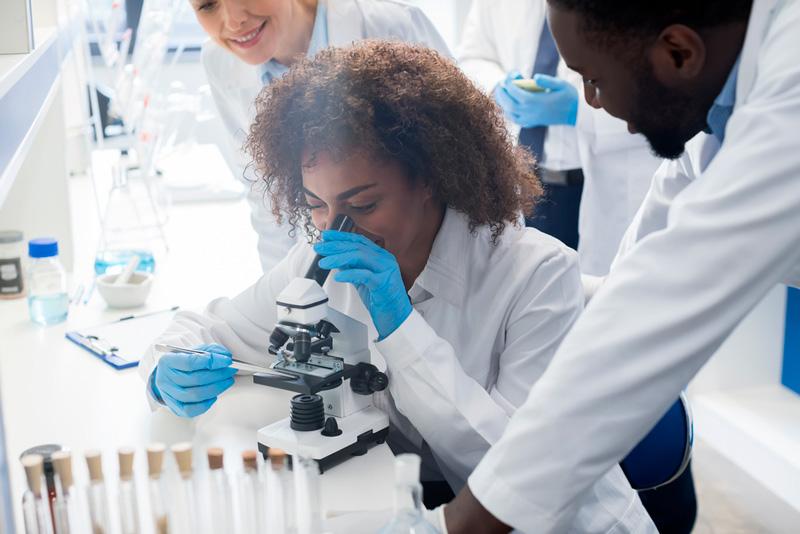 Scientists examining through microscope