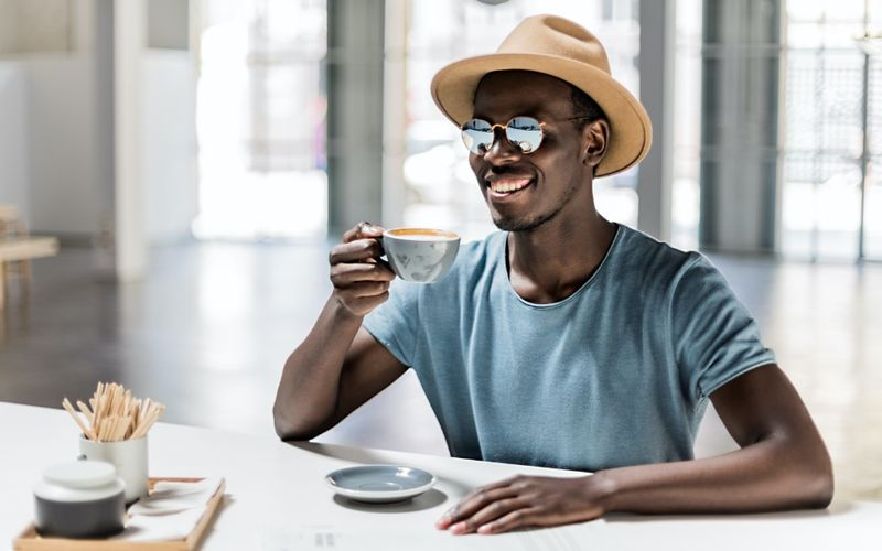 Smiling black man enjoying a cup of coffee
