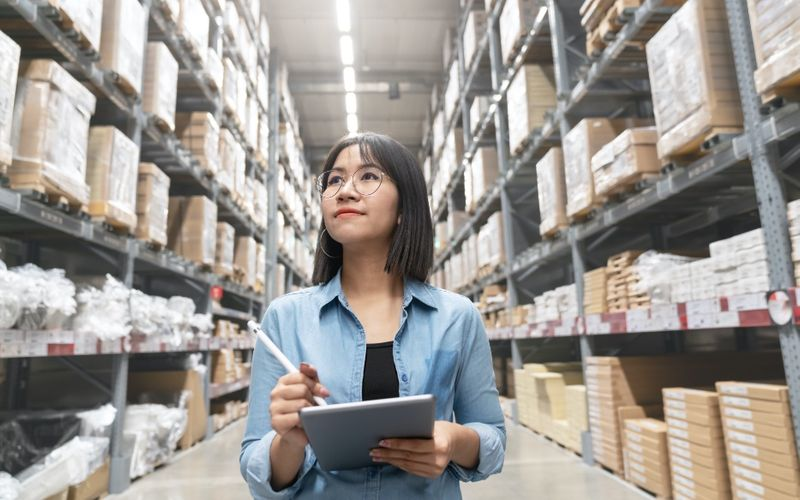 Asian business woman walking around in a warehouse