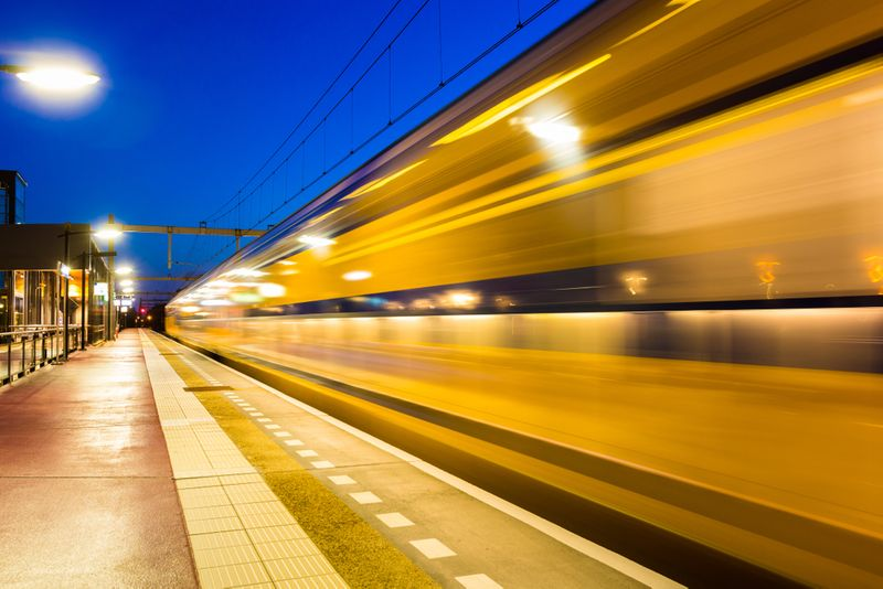 blurred yellow and blue train | immigrate to Canada