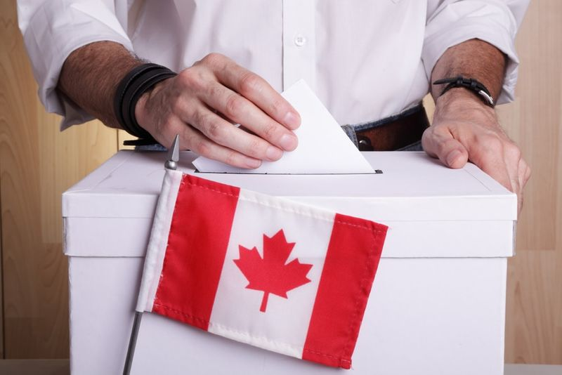 A Canadian citizen inserting a ballot into a ballot box. Canada flag in front of it | permanent residence Express Entry
