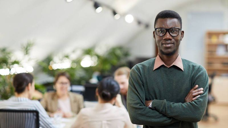 African-American-intern-in-office-standing-with-arms-crossed | Internship Jobs in Canada for International Students