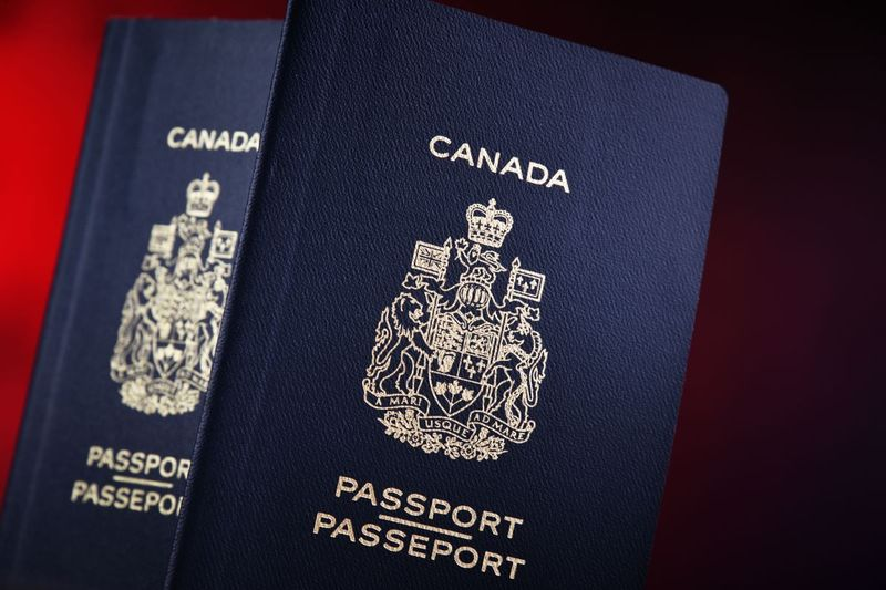 Blue Canadian passports on red background | move to Canada