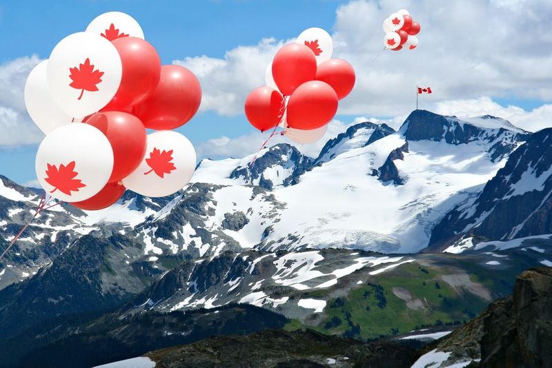 Canada day Maple leaf balloons floating over the Rocky mountains with Canadian flag in the distance