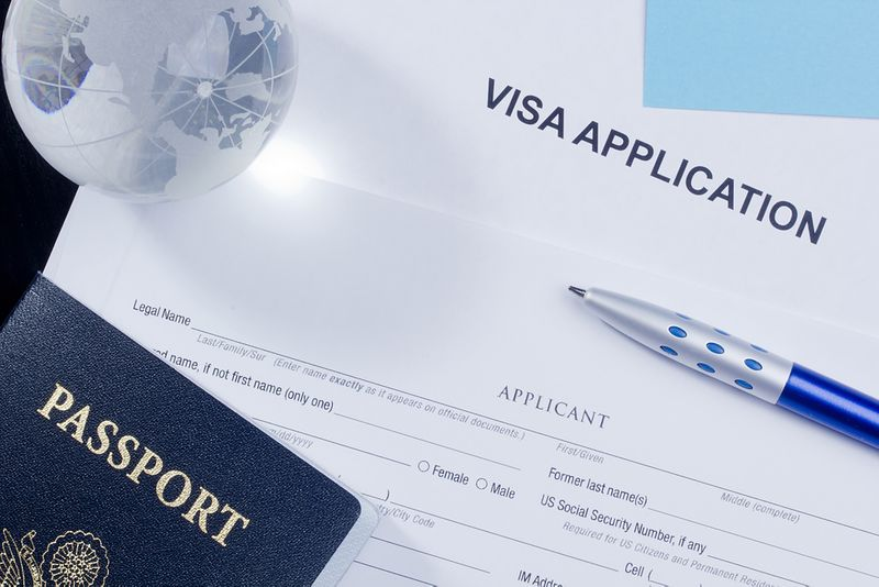Canadian visa application form with passport and glass globe