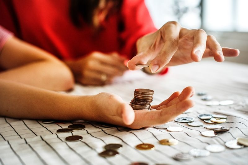 Canadian adult teaching child about money coins