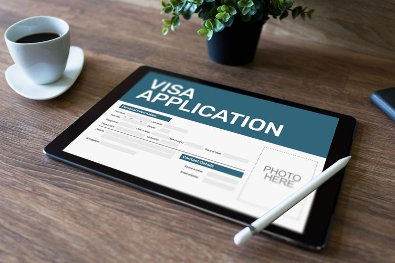 immigration application to Canada on iPad with coffee cup and pen and plant
