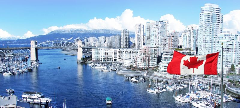 Canadian flag in front of view of False Creek and the Burrard street bridge in Vancouver Canada