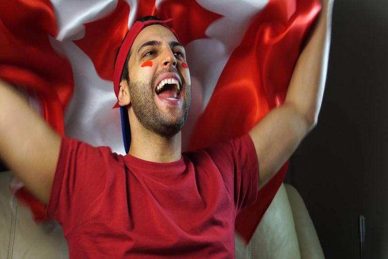 Excited man with a Canadian flag/Canadian permanent residency