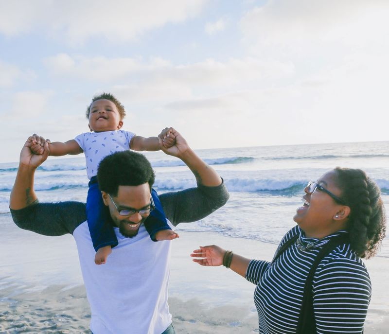 Young family with baby having fun on the beach