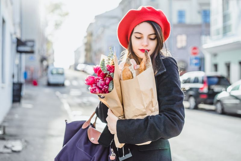 French woman walking down street with baguettes and flowers in Canada