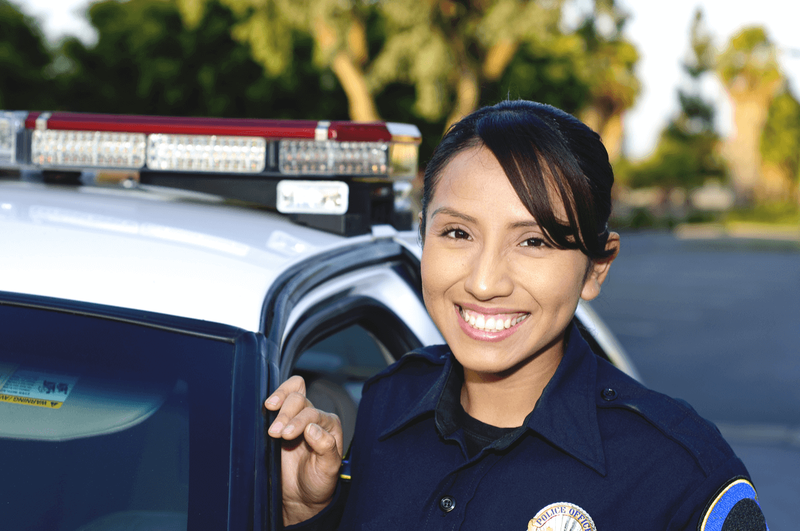 Young Hispanic police officer next to police car