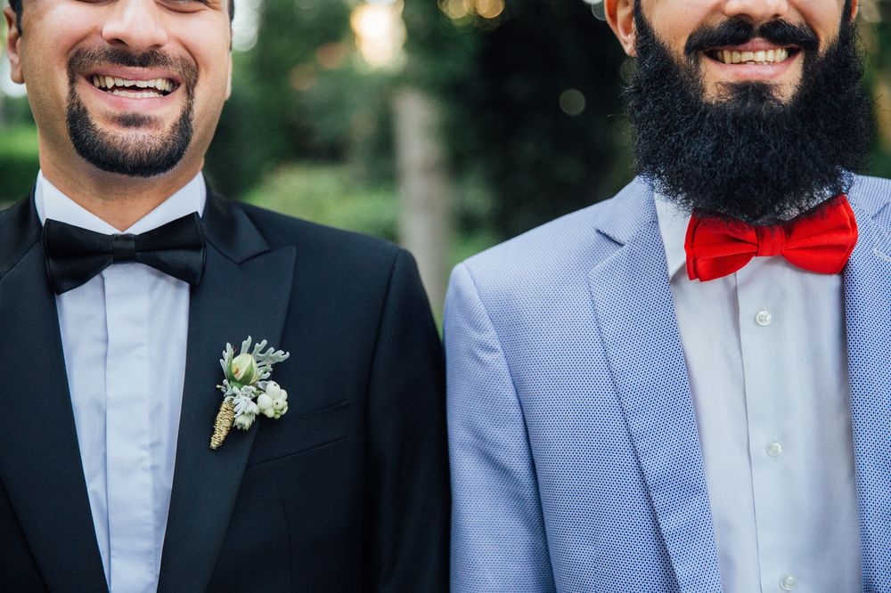 Two smilling bearded men wearing smart suits and bowties