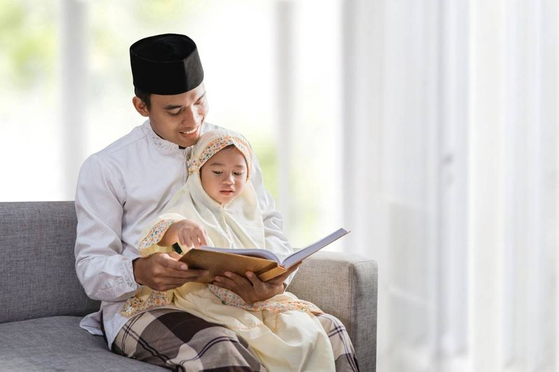 Malaysian man reading a book with child   how to apply for a Canadian visa from Malaysia
