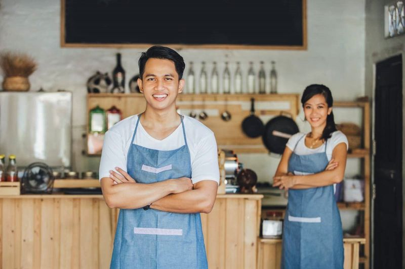Malaysian man with woman at his small restaurant business    how to apply for a Canadian visa from Malaysia