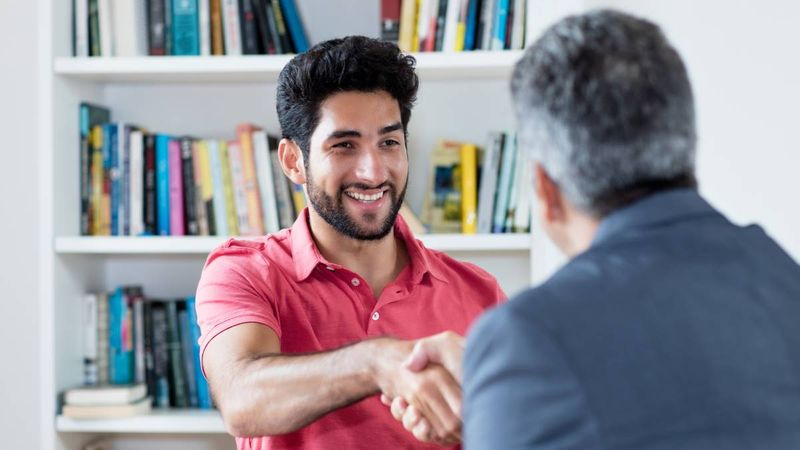 happy-smiling-Mexican-man--shaking-consultants-hand |  CUMSA Canadian Work Permit
