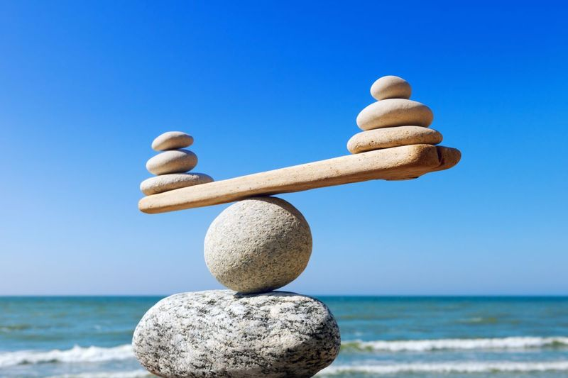 Symbolic scales of stones on the background of the sea and blue sky. Concept of harmony and balance. Pros and cons concept