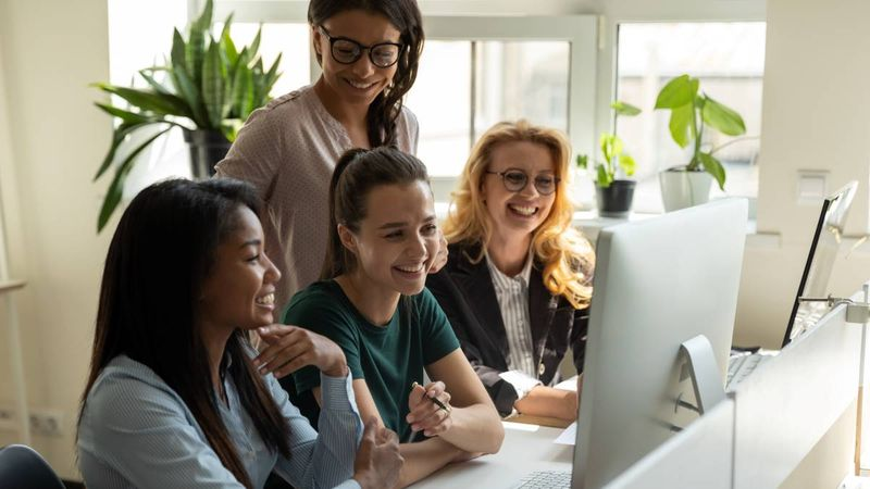 Smiling-multiracial-diverse-female-colleagues-at-desk-working-on-computer-in-office | Internship Jobs in Canada for International Students