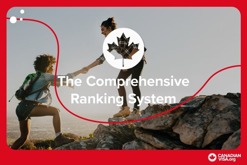 Two women helping each other up cliff while hiking | Comprehensive Ranking System | Canada Express Entry