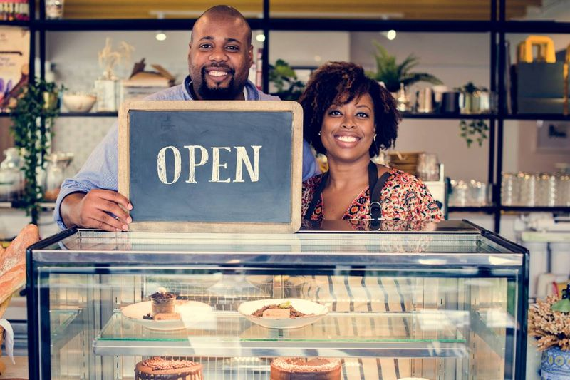 Couple entrepreneurs in cafe with open sign | British Columbia Provincial Nominee Program