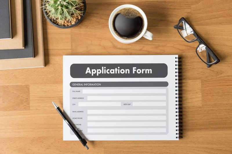 application form books coffee glasses plant and pen on desk | work in Canada