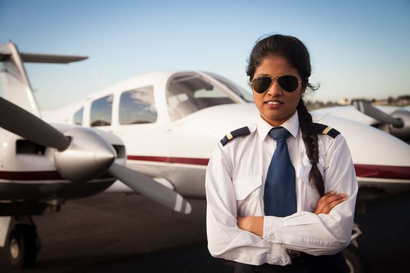 Asian Indian female pilot in front of airplane