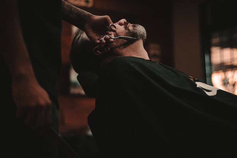 barber trimming man's beard