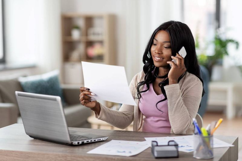 beautiful African American woman on cellphone holding form in front of laptop | immigrate to Canada